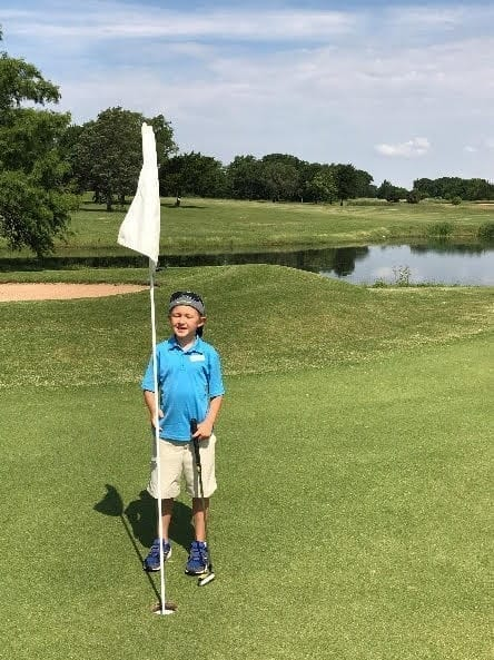 Young person at golf hole.
