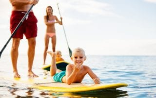 Young boy on paddleboard with parents.